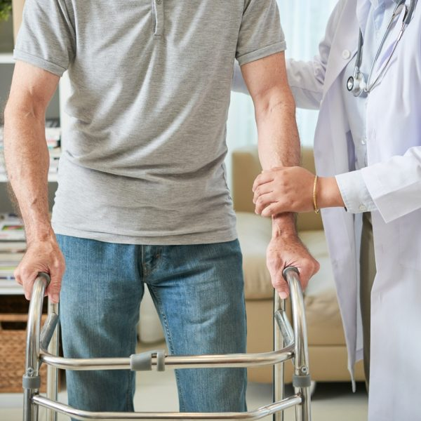 Faceless shot of senior man in disability standing with metal walker and trying to walk with help of doctor