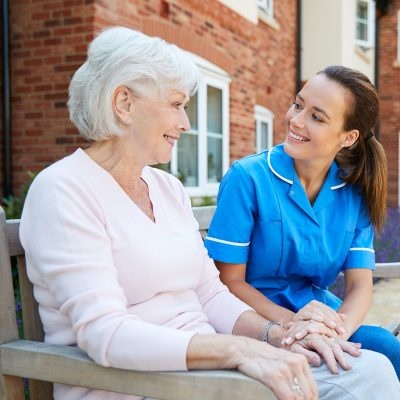 Senior,Woman,Sitting,On,Bench,And,Talking,With,Nurse,In