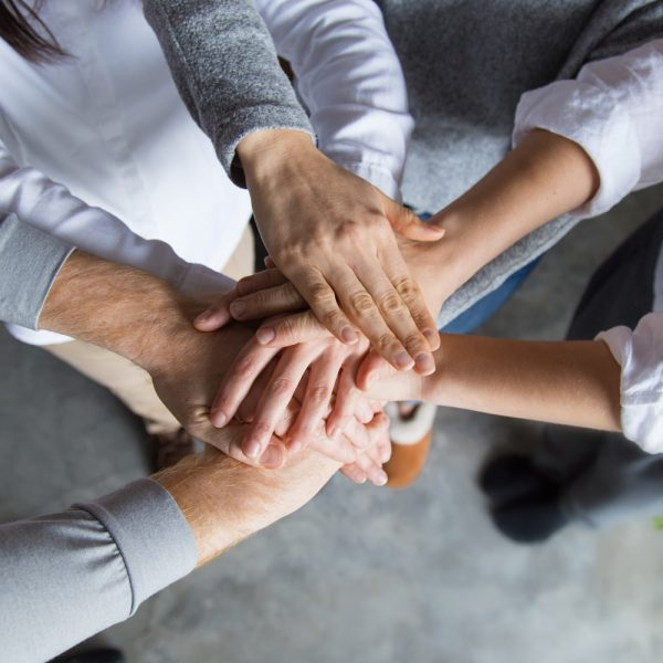 Four team members expressing togetherness and integrity. Closeup of stack of hands. Team concept